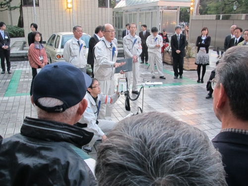 Photograph of the staff explaining the radioactivity measurement to participant in front of government building
